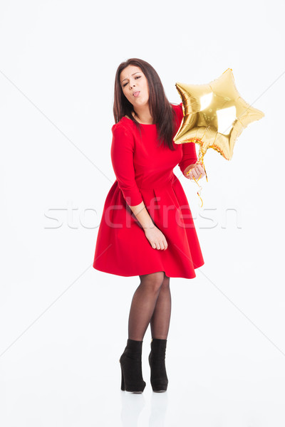 Woman in red dress holding balloon and showing tonque Stock photo © deandrobot