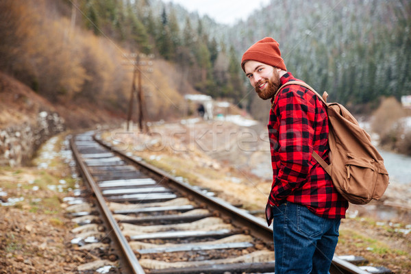Cheerful man with backpack walking along railroad in mountains Stock photo © deandrobot