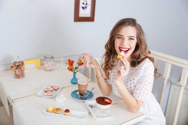 Happy woman eating small cakes and drinking latte in cafe Stock photo © deandrobot