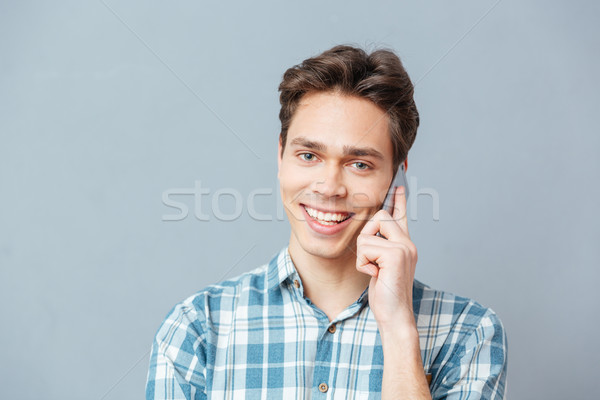 Smiling casual man talking on the phone Stock photo © deandrobot