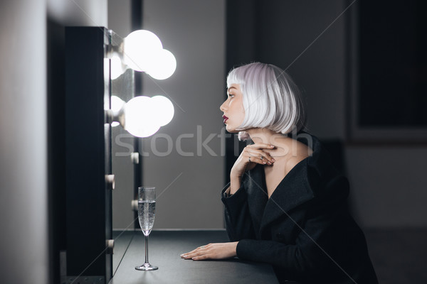 Blonde woman sitting and looking at mirror in dressing room Stock photo © deandrobot