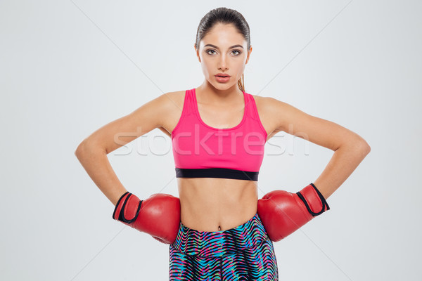 Serious sports woman in boxing gloves looking at camera Stock photo © deandrobot