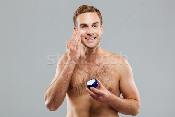Smiling man putting cream lotion on face Stock photo © deandrobot