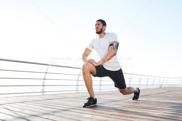 Sportsman stretching legs and listening to music from smartphone Stock photo © deandrobot