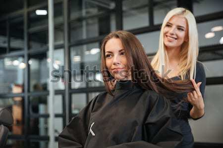 Stylist drying woman hair in beauty salon Stock photo © deandrobot