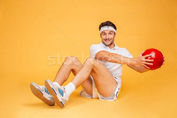 Sports man working out with fitness ball isolated Stock photo © deandrobot