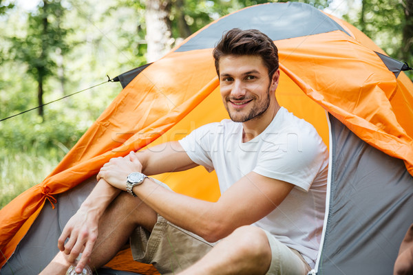 Cheerful young man tourist sitting in touristic tent Stock photo © deandrobot