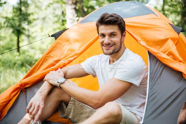 Derűs fiatalember turista ül turisztikai sátor Stock fotó © deandrobot
