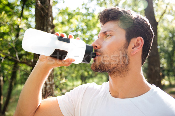 Attractive young sportsman standing and drinking water outdoors Stock photo © deandrobot