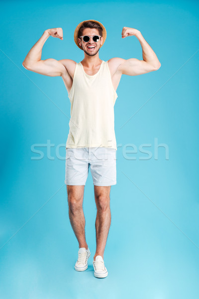 Full length of happy young man standing and showing biceps Stock photo © deandrobot