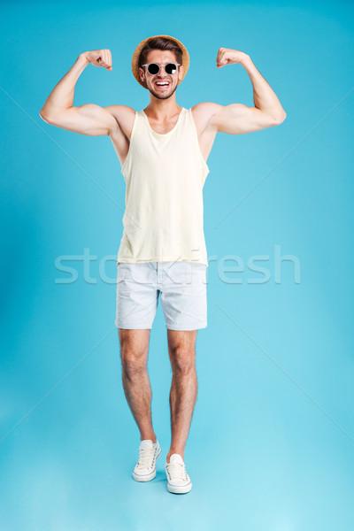 Gelukkig jonge man permanente tonen biceps Stockfoto © deandrobot