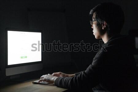 Koncentruje asian młody człowiek pracy komputera ciemne Zdjęcia stock © deandrobot