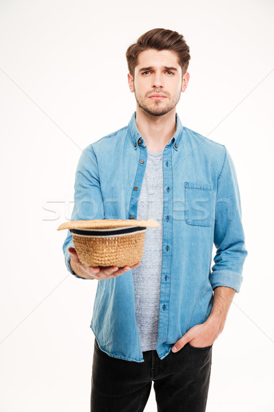 Sad poor young man holding hat and asking for money Stock photo © deandrobot