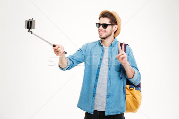 Cheerful man taking pictures with mobile phone and selfie stick Stock photo © deandrobot