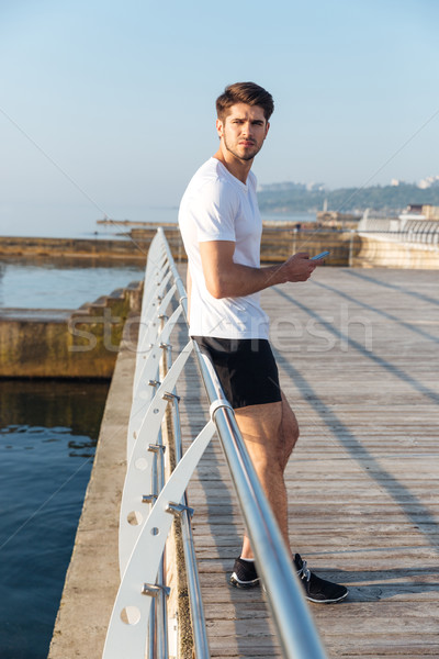 Sportsman using mobile phone standing outdoors Stock photo © deandrobot