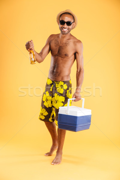 Stock photo: Cheerful young man in hat and sunglasses holding cooler bag