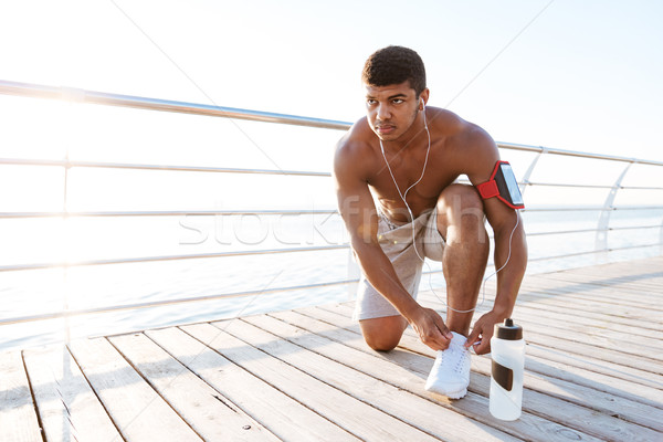 Serious african american young sportsman laces his sneakers Stock photo © deandrobot