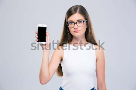 Displeased woman in pink dress making selfie photo on smartphone Stock photo © deandrobot