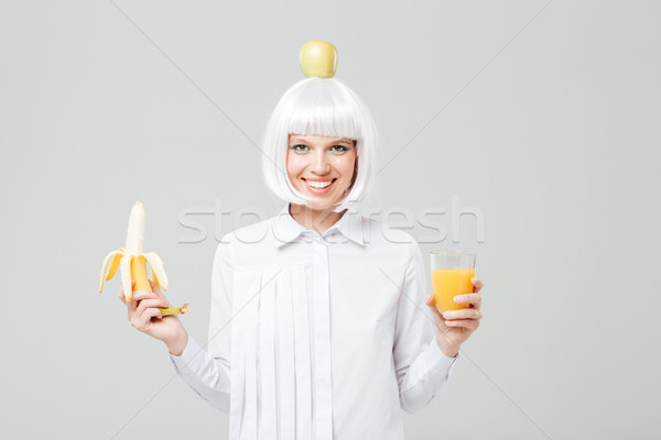 Cheerful young woman holding banana and glass of juice Stock photo © deandrobot