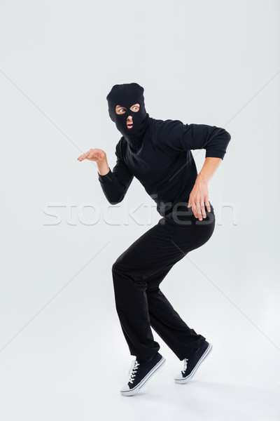 Funny scared criminal young man in balaclava running out Stock photo © deandrobot