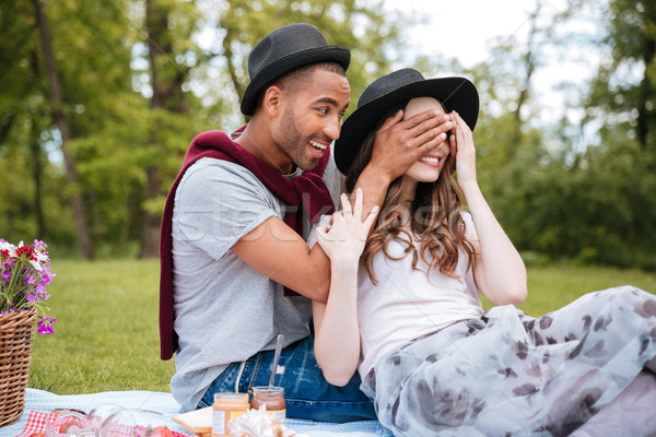 Cheerful young man covered eyes of his girlfriend in park Stock photo © deandrobot