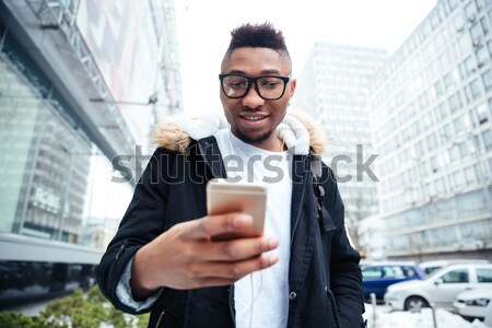 Handsome young man with magazine drinking coffee in outdoor cafe Stock photo © deandrobot