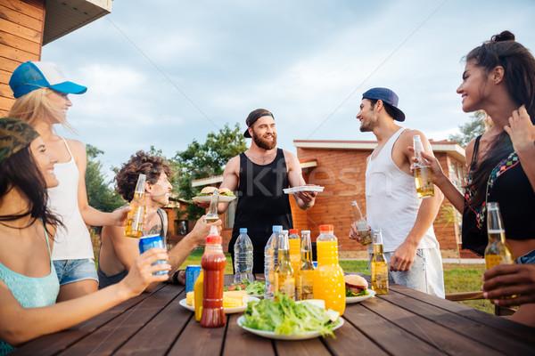 Blijde jongeren eten drinken tabel buitenshuis Stockfoto © deandrobot
