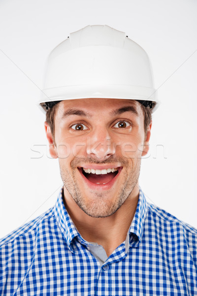Portrait of cheerful excited young man architect in hard hat Stock photo © deandrobot