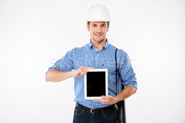 Cheerful man builder in hard hat showing blank screen tablet Stock photo © deandrobot