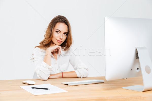 Atraente jovem empresária sessão mesa de escritório laptop Foto stock © deandrobot