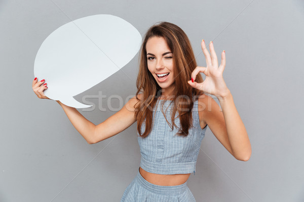 Cute woman with speech bubble winking and showing ok sign Stock photo © deandrobot