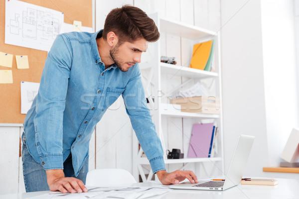 Peinzend jonge zakenman met behulp van laptop permanente kantoor Stockfoto © deandrobot