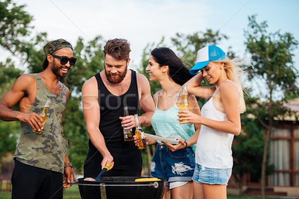 Happy people standing and frying meet on barbeque grill outdoors Stock photo © deandrobot