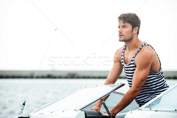 Young bearded sailor man driving his motor boat Stock photo © deandrobot