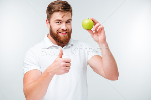 Happy man holding green apple and showing thumbs up gesture Stock photo © deandrobot