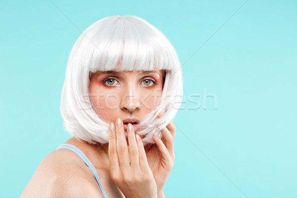 Portrait of amazed pretty young woman in blonde wig Stock photo © deandrobot