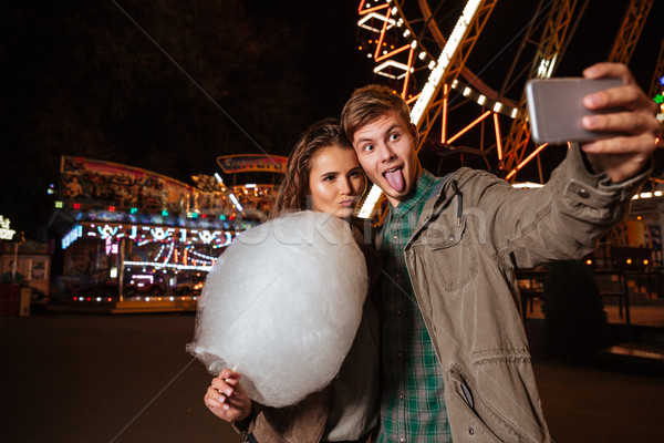 Couple making funny faces and taking selfie in amusement park Stock photo © deandrobot