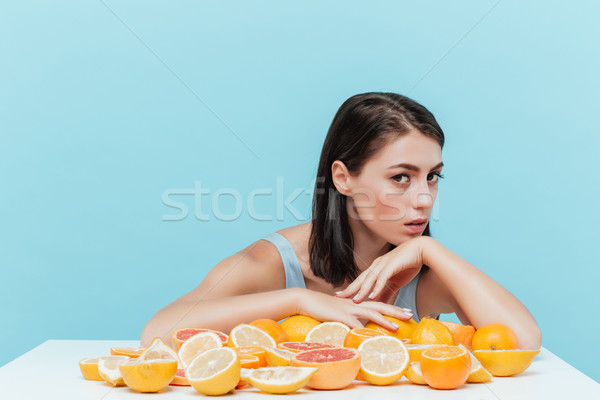 Woman sitting at table with oranges and grapefruits Stock photo © deandrobot