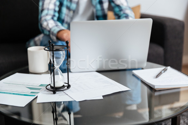 Cropped photo of man using laptop. Focus on hourglass. Stock photo © deandrobot