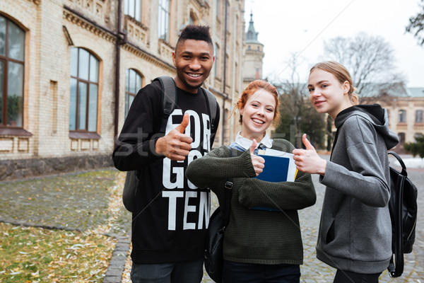 Multiethnic students standing in university campus and showing thumbs up Stock photo © deandrobot