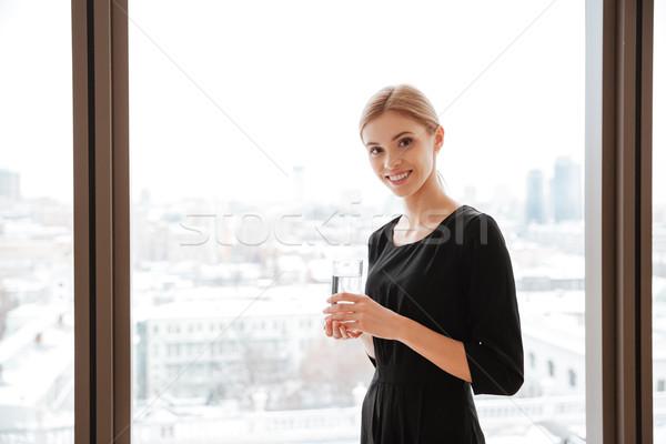 Fiatal hölgy munkás tart üveg víz Stock fotó © deandrobot