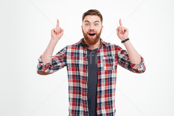 Portrait of excited man in checkered shirt pointing fingers up Stock photo © deandrobot