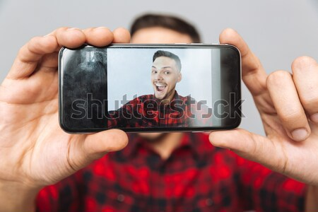 Man in plaid shirt pointing finger at blank tablet screen Stock photo © deandrobot
