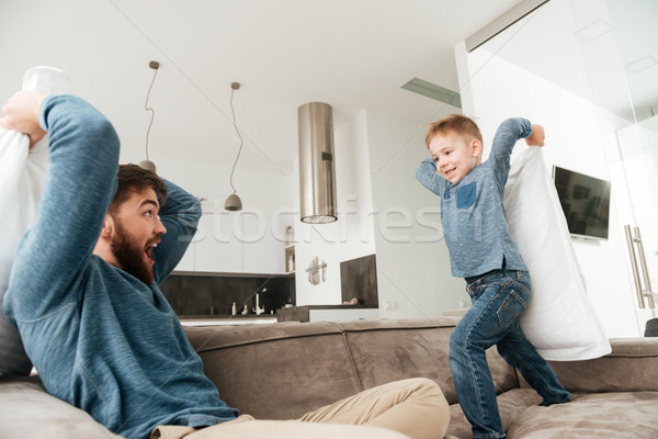 Young father fighting by pillows with his little cute son. Stock photo © deandrobot