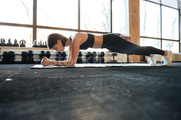 Woman athlete training and doing plank exercise in gym Stock photo © deandrobot