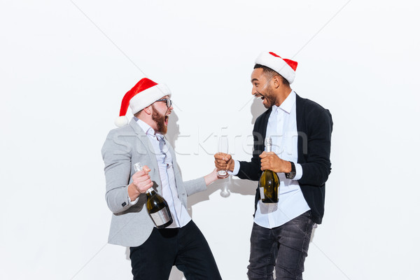 Two happy men in santa hats drinking champagne and laughing Stock photo © deandrobot