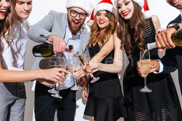 People in santa hats standing and pouring champagne into glasses Stock photo © deandrobot