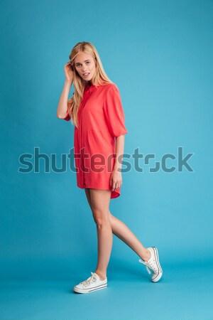 Full length portrait of a beautiful woman walking at studio Stock photo © deandrobot