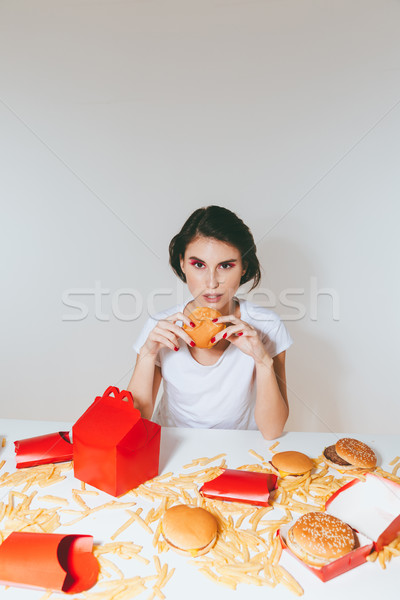 Charming woman eating hamburger from red box at the table Stock photo © deandrobot