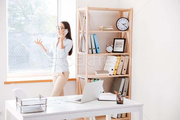 Young beautiful businesswoman talking by phone in office Stock photo © deandrobot